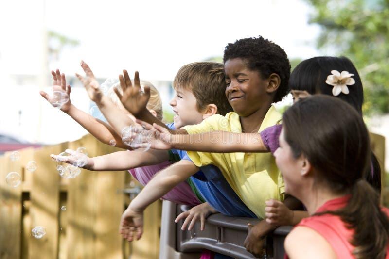 Gruppo di giovane gioco prescolare dei bambini immagini stock libere da diritti
