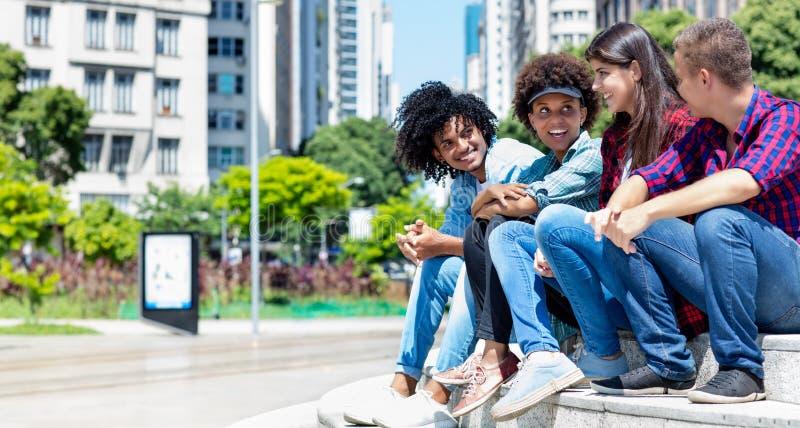 Gruppo di giovani adulti di conversazione dei pantaloni a vita bassa nella città fotografie stock libere da diritti
