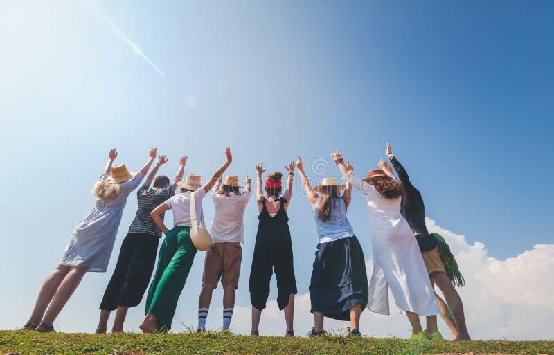 Gruppo di giovani alla moda allegri felici contro cielo blu, amicizia, valori della comunità, fotografie stock