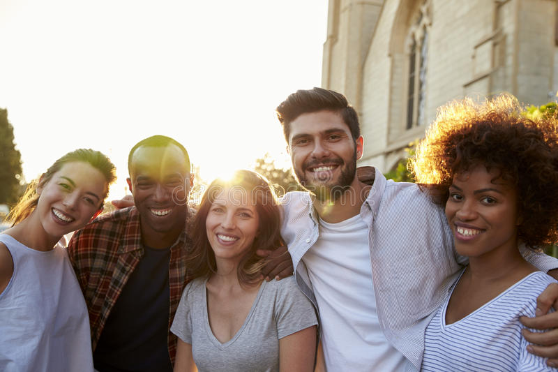Gruppo di giovani amici adulti sorridenti che abbracciano nella via immagine stock libera da diritti