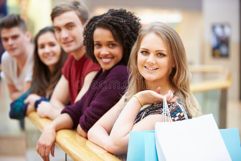 Gruppo di giovani amici che comperano insieme nel centro commerciale fotografia stock libera da diritti