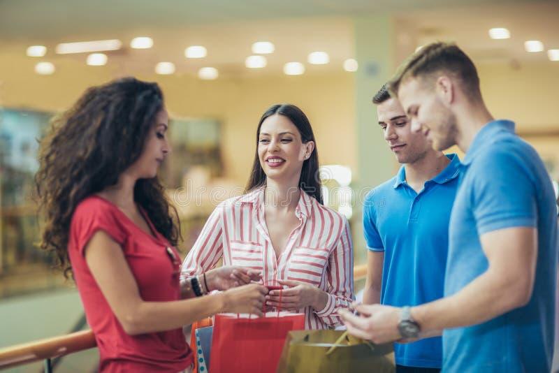 Gruppo di giovani amici che comperano nel centro commerciale fotografia stock