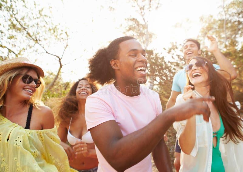 Gruppo di giovani amici che hanno partito sulla spiaggia insieme immagini stock libere da diritti