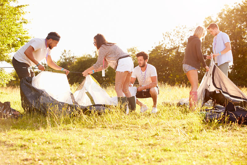Gruppo di giovani amici che lanciano le tende vacanza in campeggio fotografia stock