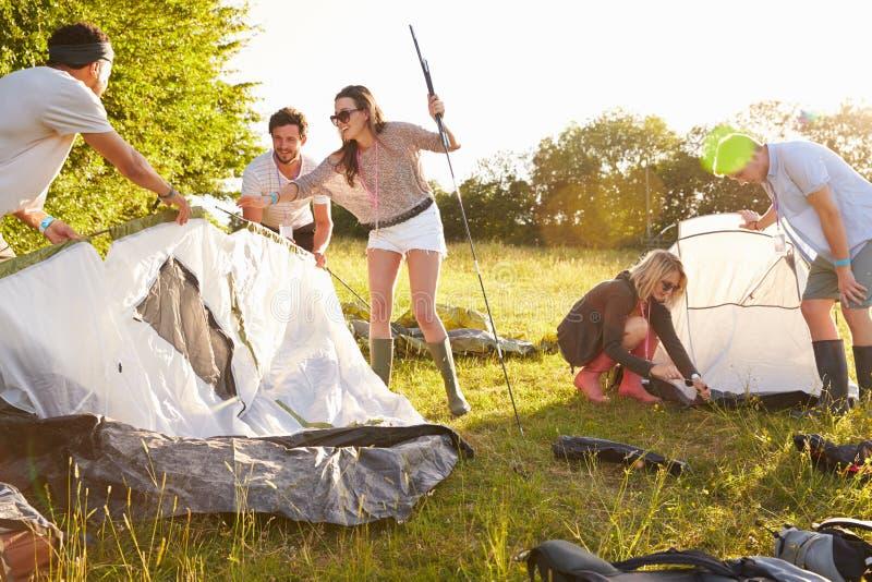 Gruppo di giovani amici che lanciano le tende vacanza in campeggio immagine stock