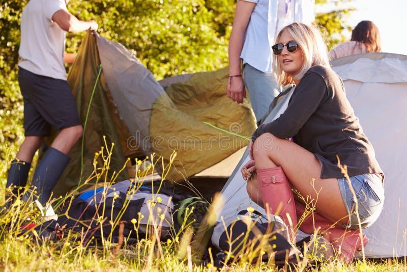 Gruppo di giovani amici che lanciano le tende vacanza in campeggio fotografia stock libera da diritti