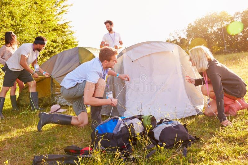 Gruppo di giovani amici che lanciano le tende vacanza in campeggio immagini stock