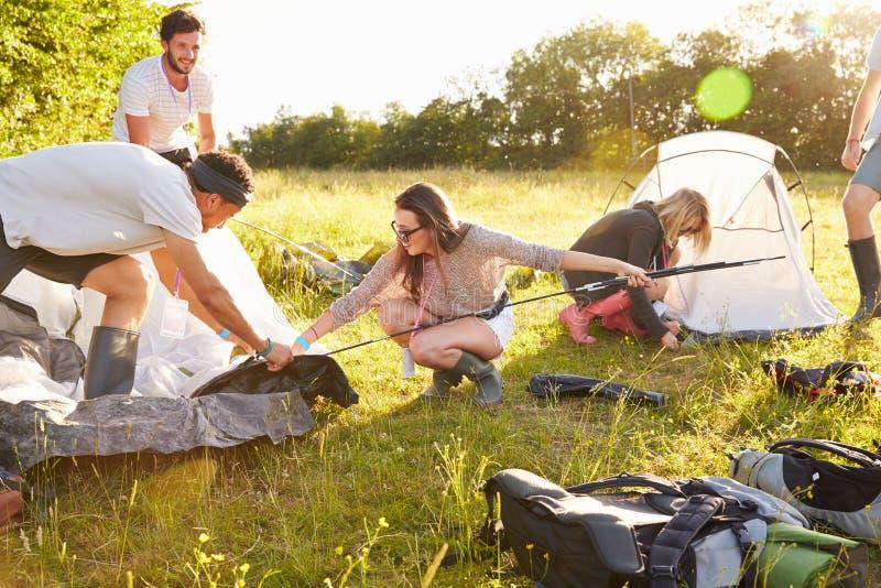 Gruppo di giovani amici che lanciano le tende vacanza in campeggio fotografie stock