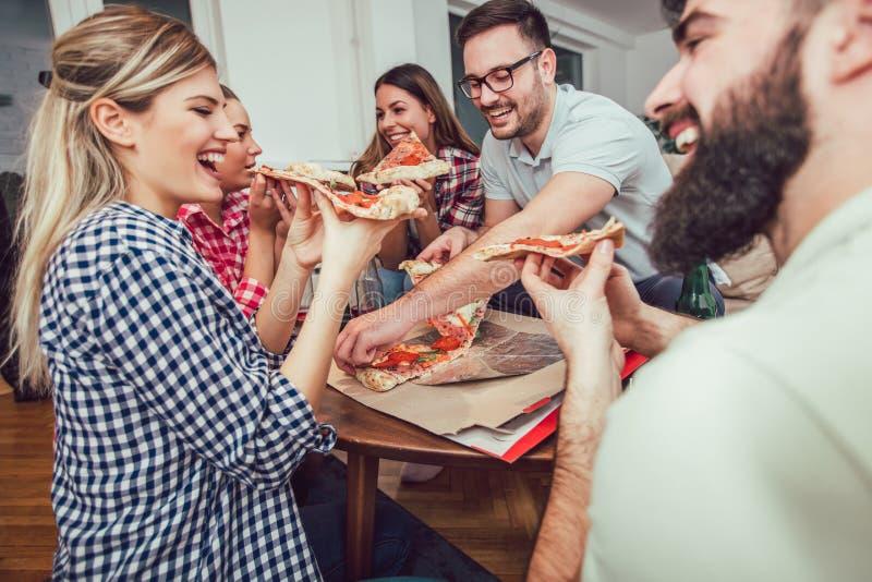 Gruppo di giovani amici che mangiano pizza fotografia stock libera da diritti