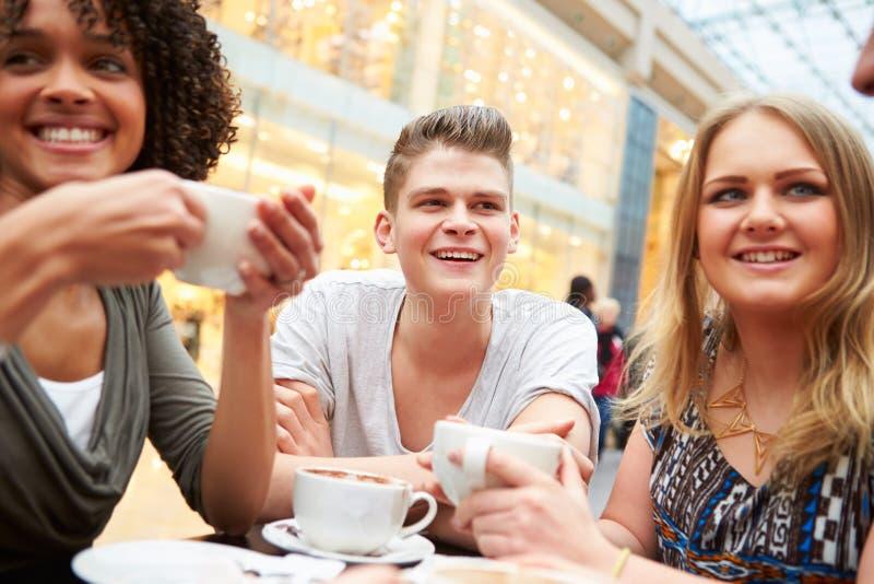 Gruppo di giovani amici che si incontrano in caffè fotografia stock libera da diritti