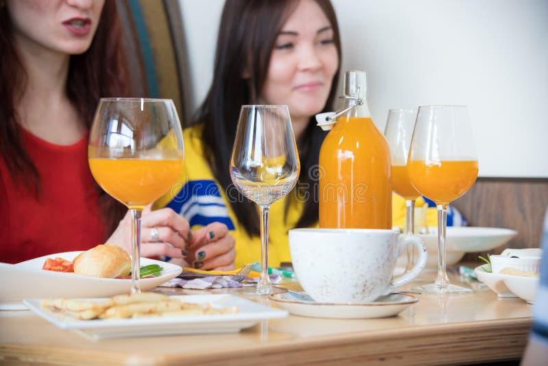 Gruppo di giovani amici che si siedono in caffè Una bottiglia con succo fotografie stock