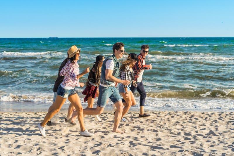 Gruppo di giovani amici dei pantaloni a vita bassa che corrono insieme lungo la spiaggia immagini stock