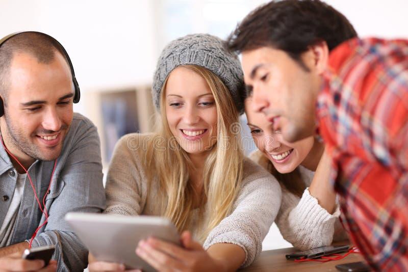 Gruppo di giovani amici divertendosi facendo uso della compressa fotografia stock