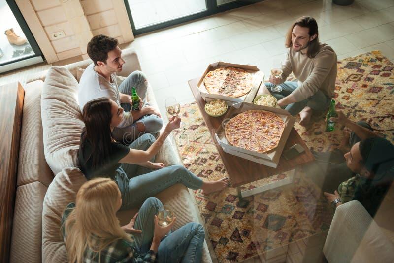 Gruppo di giovani amici felici che riposano a casa immagini stock libere da diritti
