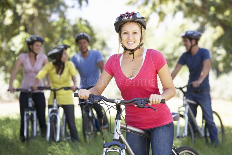 Gruppo di giovani amici sul giro del ciclo in campagna immagine stock