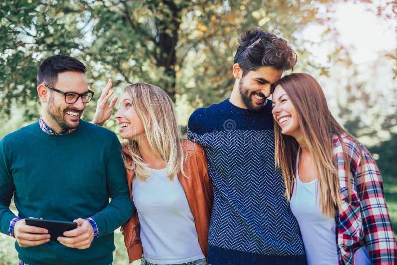 Gruppo di giovani che camminano attraverso il parco immagine stock