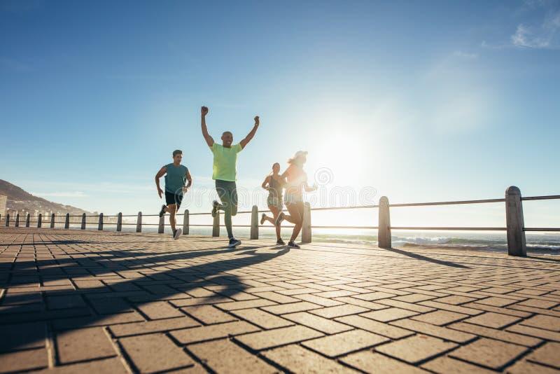 Gruppo di giovani che corrono lungo la spiaggia fotografia stock libera da diritti