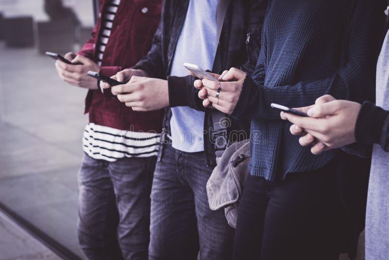 Gruppo di giovani che guardano i telefoni cellulari astuti al underg immagine stock libera da diritti