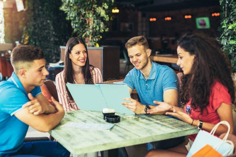 Gruppo di giovani che si incontrano in un caffè fotografia stock