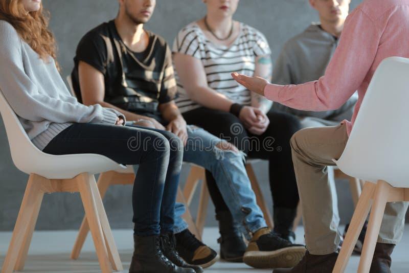 Gruppo di giovani che si siedono in un cerchio e che parlano con psicoanalizzare immagini stock libere da diritti