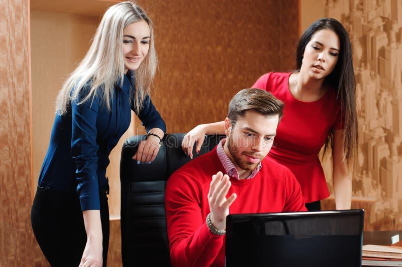 Gruppo di giovani colleghi che per mezzo del computer portatile all'ufficio fotografie stock