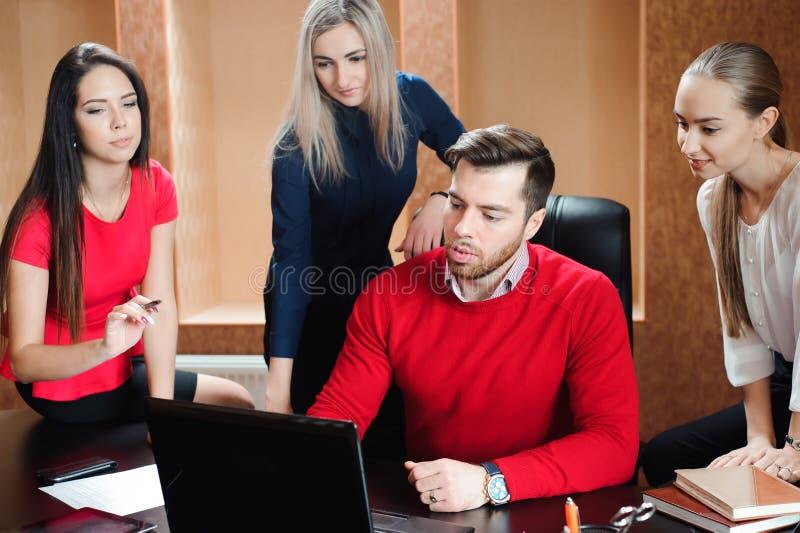Gruppo di giovani colleghi che per mezzo del computer portatile all'ufficio fotografie stock libere da diritti