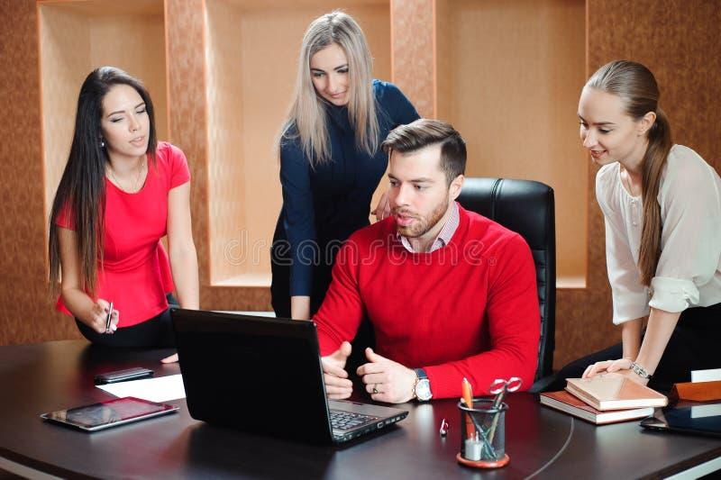 Gruppo di giovani colleghi che per mezzo del computer portatile all'ufficio immagine stock