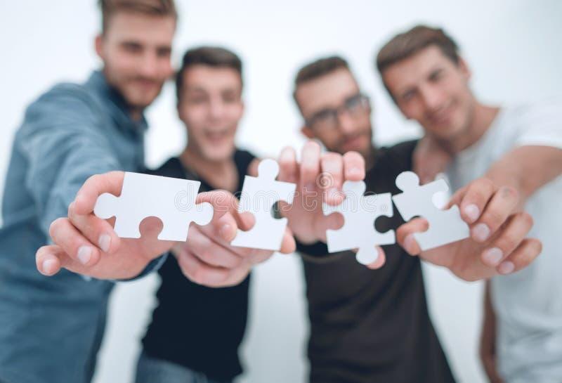 Gruppo di giovani con i pezzi di puzzle immagine stock