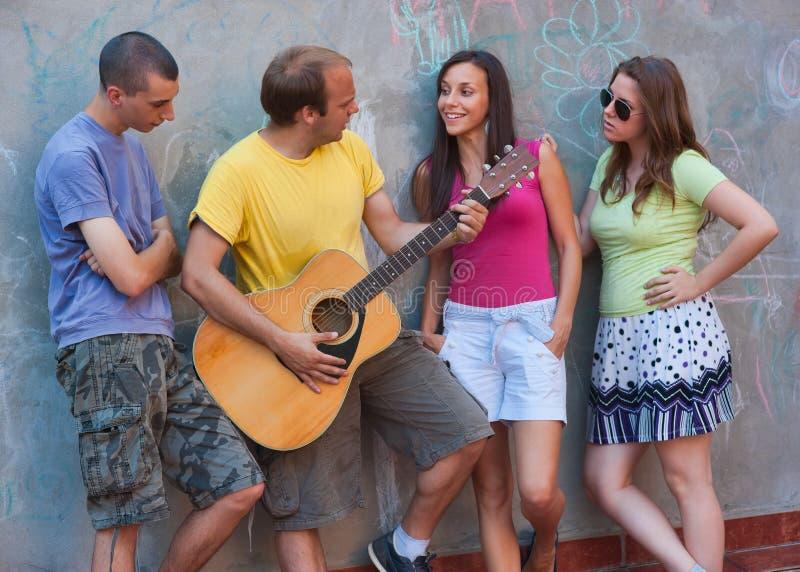 Gruppo di giovani con la chitarra immagini stock