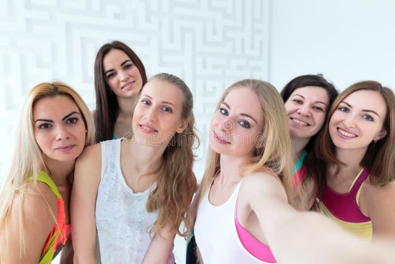 Gruppo di giovani donne attraenti vestite in abiti sportivi che prendono selfie fotografie stock