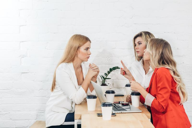 Gruppo di giovani donne che discutono progetto creativo durante il processo del lavoro immagini stock