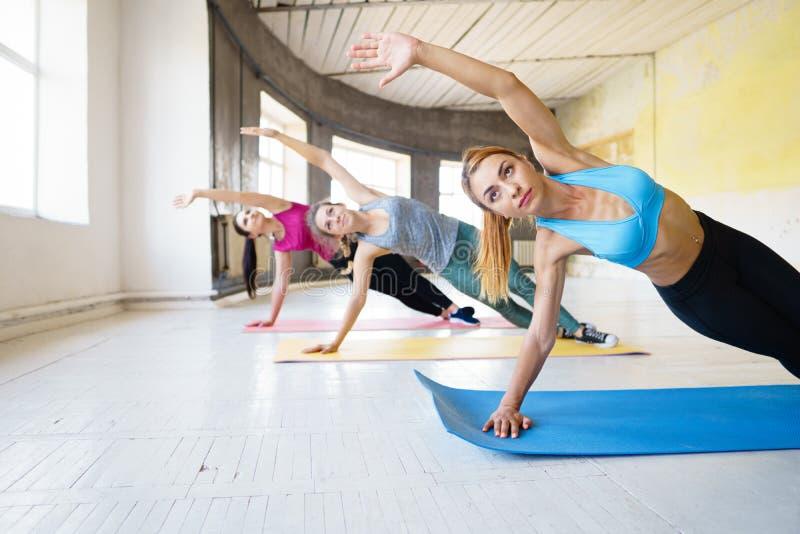 Gruppo di giovani donne sportive che praticano yoga con l'istruttore, standi fotografie stock