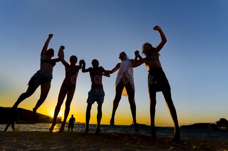 Gruppo di giovani felici che ballano alla spiaggia fotografia stock