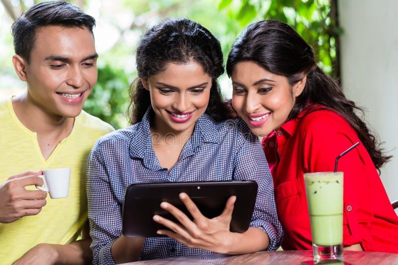 Gruppo di giovani indiani che esaminano il computer della compressa immagine stock libera da diritti
