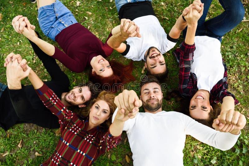 Gruppo di giovani insieme all'aperto nel fondo urbano fotografia stock