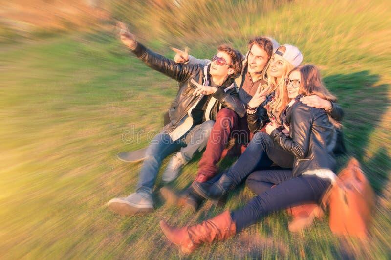 Gruppo di giovani migliori amici dei pantaloni a vita bassa che prendono un selfie all'aperto fotografie stock