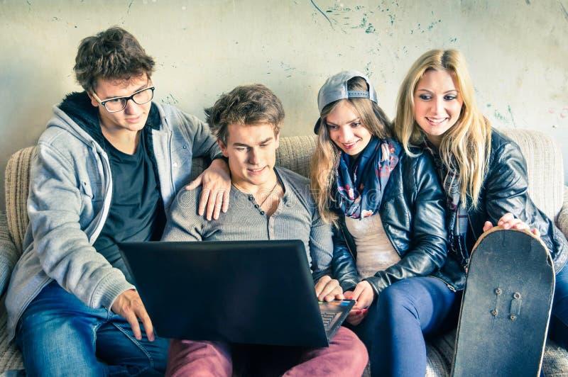 Gruppo di giovani migliori amici dei pantaloni a vita bassa con il computer fotografie stock libere da diritti