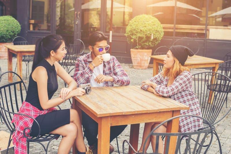Gruppo di giovani pantaloni a vita bassa che si siede in un caffè, giovani amici allegri immagine stock libera da diritti