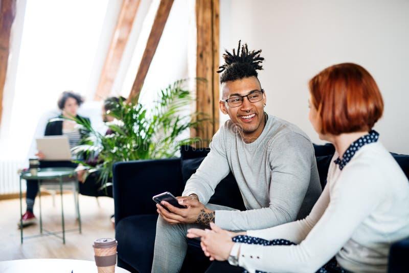 Gruppo di giovani persone di affari che parlano nell'ufficio, concetto di partenza immagini stock libere da diritti