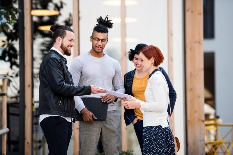 Gruppo di giovani persone di affari che stanno all'aperto nel cortile, parlante immagini stock libere da diritti