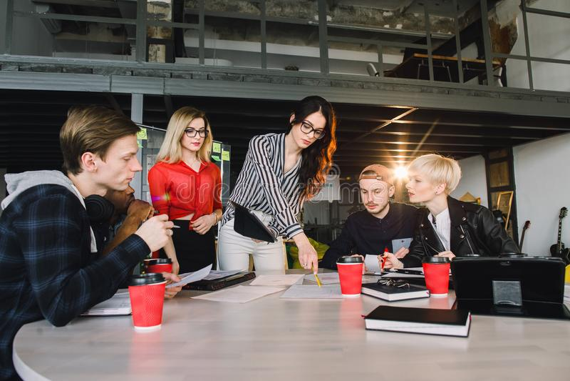 Gruppo di giovani professionisti di affari che utilizzano tecnologia in una riunione informale impegnato su progettazione dell'ar immagine stock libera da diritti