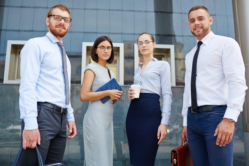 Gruppo di giovani professionisti di affari fuori dell'edificio per uffici immagine stock