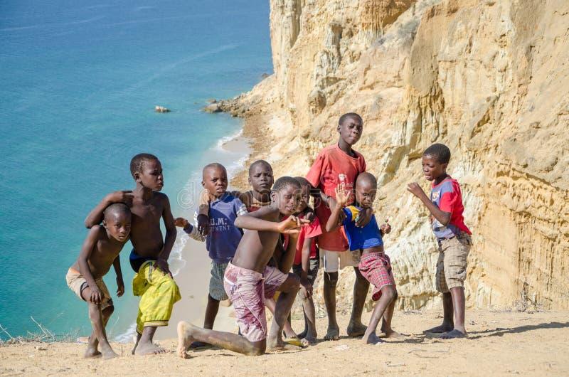 Gruppo di giovani ragazzi africani che posano davanti alla linea ed all'oceano spettacolari della costa del deserto alla Praia da immagine stock libera da diritti