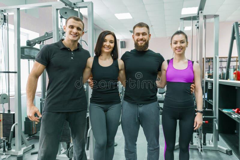 Gruppo di giovani sorridenti di sport che abbracciano insieme nella palestra di forma fisica Forma fisica, sport, lavoro di squad fotografie stock