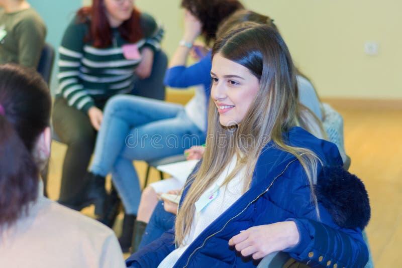 Gruppo di giovani studentesse dell'università che hanno una discussione di gruppo che si siede insieme su un cerchio delle sedie immagine stock libera da diritti