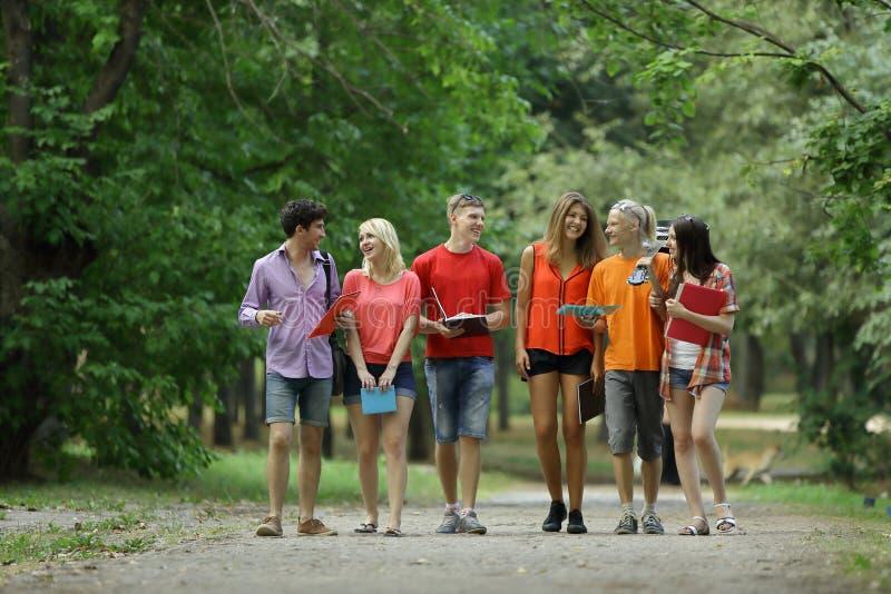 Gruppo di giovani studenti che camminano insieme in un campus universitario della High School fotografia stock
