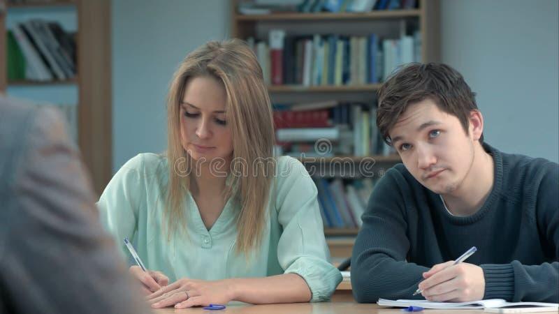 Gruppo di giovani studenti che scrivono le note nell'aula immagine stock libera da diritti