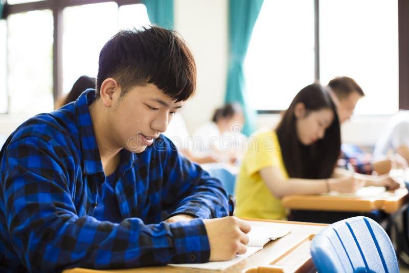 Gruppo di giovani studenti che scrivono le note nell'aula fotografia stock libera da diritti