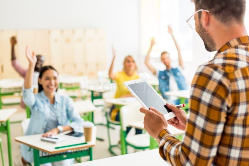 gruppo di giovani studenti che sollevano sulle mani per rispondere sulla domanda degli insegnanti mentre lui che sta con la compr fotografia stock