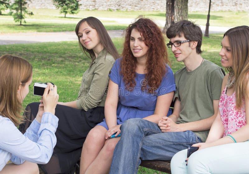 Gruppo di giovani studenti di college felici che prendono una foto immagini stock